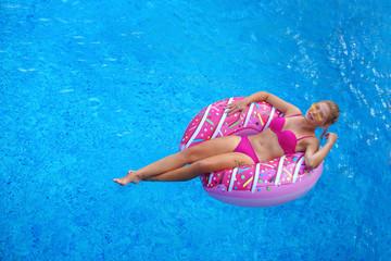 happy girl in pink bikini swimming on inflatable donut mattress