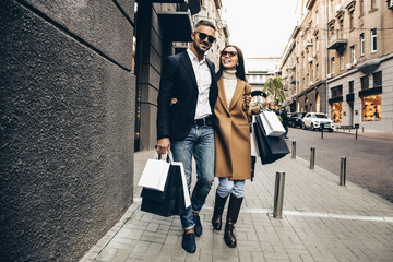 Shopping. Black Friday. Couple. Love. Man and woman with shopping bags are hugging and smiling while walking down the street