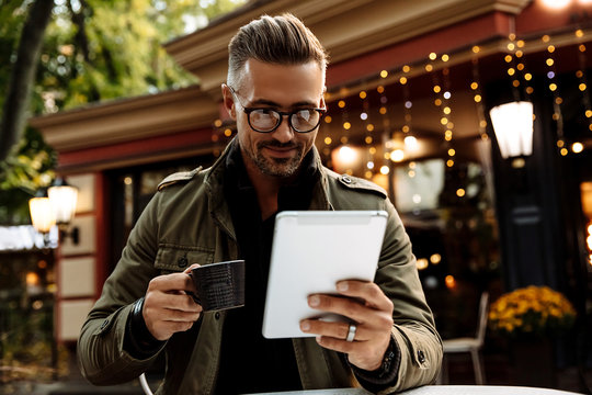 Technology. Cafe. Man in warm casual clothes is using a tablet, holding a cup of coffee and smiling while sitting in the cafe outdoors