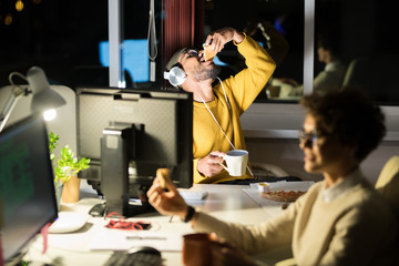 Portrait of Middle-Eastern young man working in office at night and eating snacks