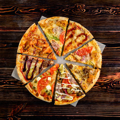 different pizza pieces laid out in the shape of a round pizza on a wooden background