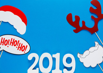 numbers 2019 and photo booth colorful props for christmas party on blue background. Christmas and New year decorations