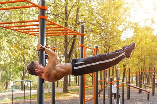 Athletic guy doing gymnastics outdoor
