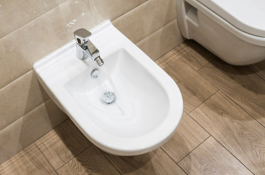 Details of white ceramic bidet with a running water in modern bathroom.