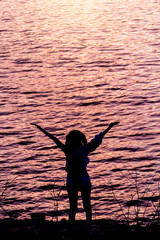 Happy celebrating winning success woman at sunset.Silhouette
