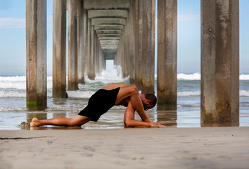 Male Yoga Instructor at the Beach in Lizard Lunge Pose