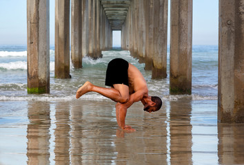 Yoga Male Instructor at the Beach in Crow Pose