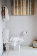 Light bathroom with toilet, towel, and wooden bin