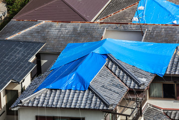 Residential buildings covered by blue sheet to prevent natural disaster