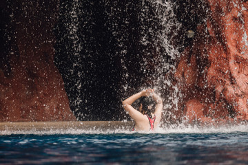 Tropical waterfall landscape in a beautiful relaxing spa resort, woman swim in the pool