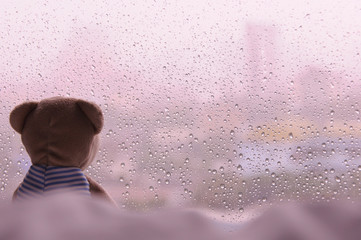 Lonely Teddy Bear sitting on bed and looking out at the window in rainy day. This photo has space background for text - vintage tone.