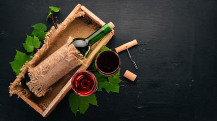 Red wine in a bottle with a glass and grapes. On a black wooden background. Free space for text. Top view.