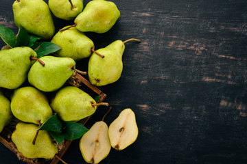 Fresh pears. A large set of pears. Fruits. Free space for text. On a black wooden background. Top view.