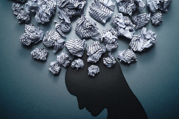 Silhouette of depressed person head. Concept image of depression and anxiety. Waste paper and head silhouette.