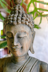 Wooden buddha image in Thai style in a traditional Thai house with blurred background