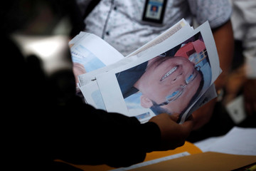 Indonesian Disaster Victim Identification (DVI) officer holds pictures and identity documents of passengers on the crashed Lion Air flight JT610, at Bhayangkara R. Said Sukanto hospital in Jakarta