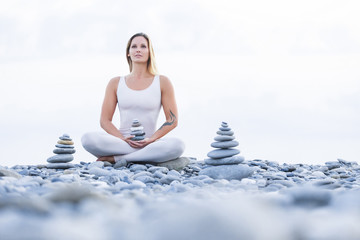 Spa and yoga concept. Beautiful young healthy woman is meditating on the stone shore, holding in hands a stone pyramid on the background of the sea on a warm summer evening