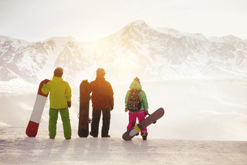 Three snowboarders stands against mountains