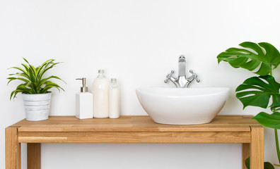 Bathroom wooden table with washbasin, faucet, plants and soap bottles