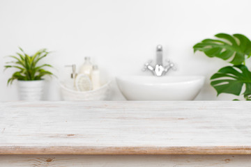 Wooden table top over blurred bathroom interior and spa products