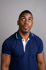 Young handsome African man wearing blue polo shirt against gray
