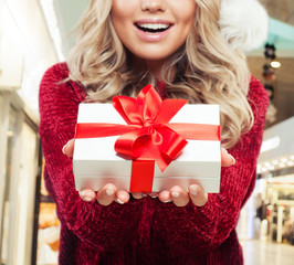 Christmas gift in female hands on shopping mall background
