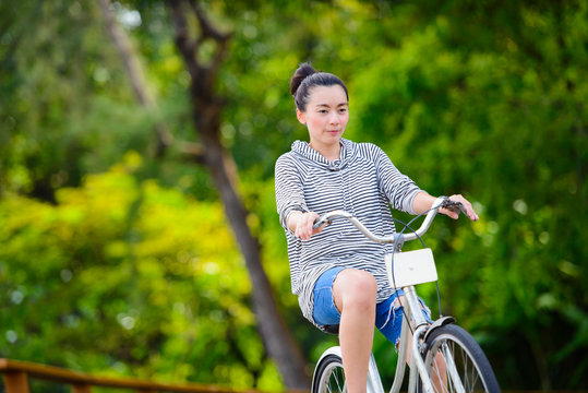 Asian woman riding a vintage bicycle in a park
