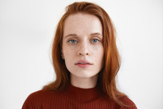 Gorgeous blue eyed red haired young European lady in maroon turtleneck looking at camera with calm facial expression, posing isolated against blank studio wall background with copyspace for your text