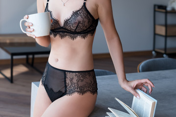 Woman in fashion lace lingerie in the kitchen drinking morning coffee.