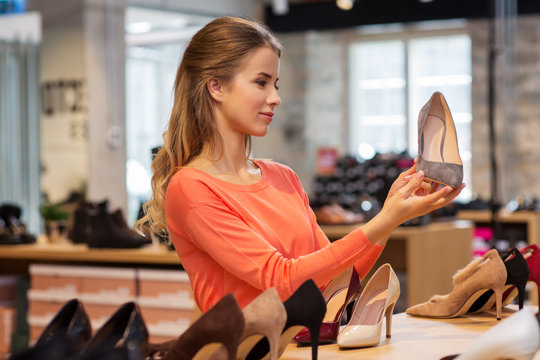 sale, shopping, fashion and people concept - young woman choosing shoes at store