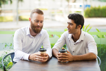 Two business men drinking coffee and chatting in outdoor cafe. People sitting at table with blurred plants in background. Coffee break concept. Front view.