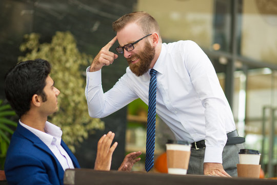 Unstable bearded boss gesturing at head while screaming at Indian employee. Annoyed businessman blaming him for problem, young man taking back and gesturing hands. Aggression concept