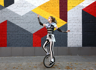 Wall Mural - Girl clown performing with a unicycle