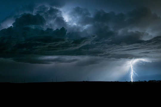 A powerful branched lightningbolt strikes down from a severe thunderstorm in Nebraska