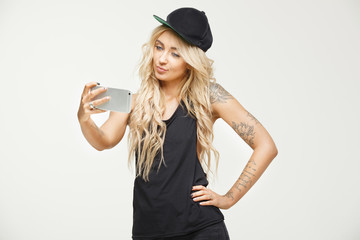 tattooed girl with blond hair stretches lips and takes selfie on phone in white isolated background. stylish woman swag look photographing themselves smartphone.