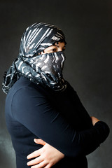 Portrait of a girl in a scarf in a black jacket on a dark background.