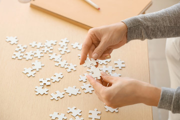 Woman assembling puzzle on wooden table
