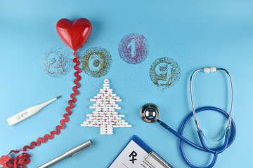 Medicine pills shape of christmas tree and others equipment of doctor on blue background. Concept christmas and new year 2019.