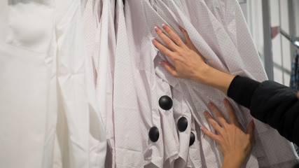 Female hands touch shirts in hangers in store. Woman shoose some clothes, close up.