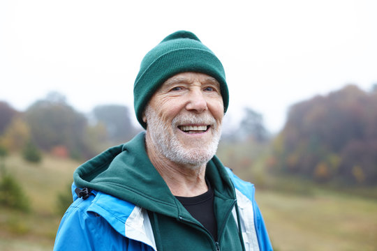 Portrait of senior countyman having walk in rural area. Cheerful elderly farmer spending time outoors. Mature retired male with beard walking in wild nature, looking at camera with happy smile