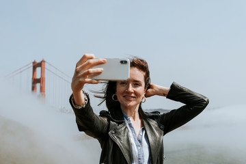 Happy woman taking a selfie with the Golden Gate Bridge, San Francisco
