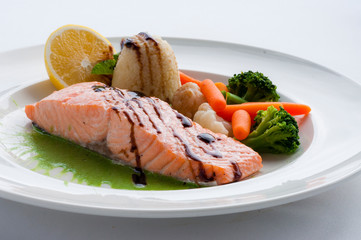 Salmon with sauce, rice, vegetables mushrooms and lemon