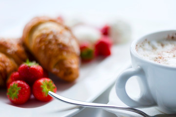 Decorated food. Croissants with strawberries and cup of coffee