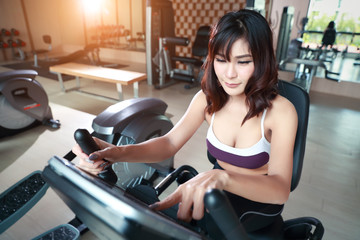 portrait of young healthy and sporty woman using exercise machine in gym (this image for fitness and workout concept)