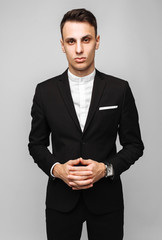 Portrait of a handsome young business man, male, in a classic black suit, on a gray background.