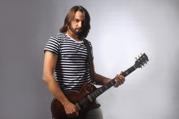 rock musician playing solo on the guitar.photo on gray background