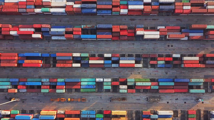 Aerial top view of container cargo ship in the export and import business and logistics international goods in urban city. Shipping cargo to the harbor by crane.