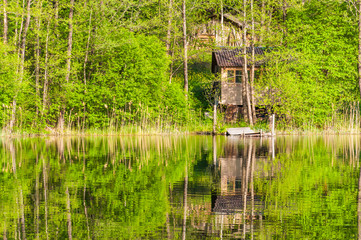 Hidden abandoned wooden cabin on forest lake coast and its reflection on water surface