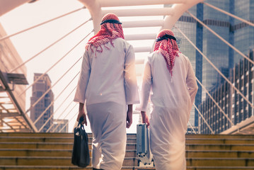 Two business people with briefcase walking together in teamwork,  Saudi Arabian business concept.