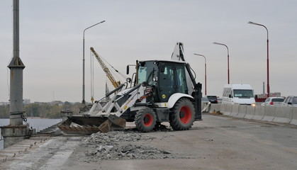 Tractor or excavator repairs bridge, removes garbage